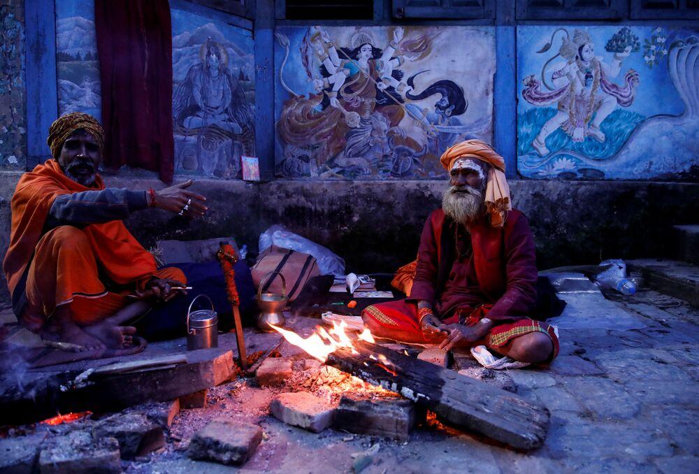 Religiosos hindus sadhus sentam ao lado de fogueira no templo de Pashupatinath, no Nepal