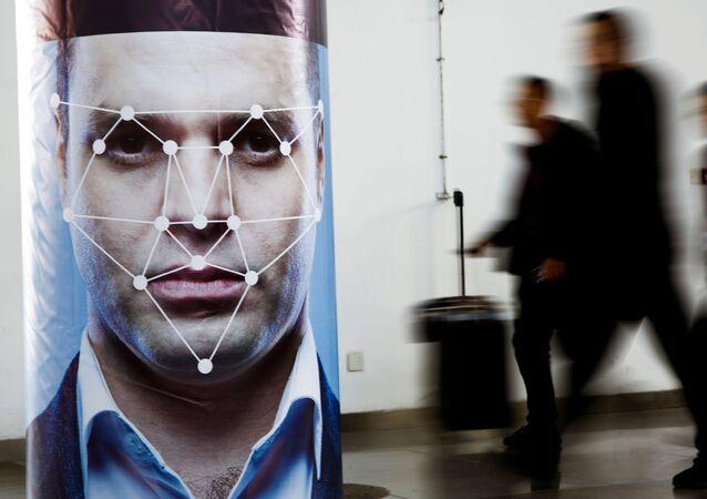 Pessoas passam por cartaz simulando um software de reconhecimento facial, em Pequim, China