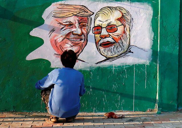 Pintor termina detalhes de obra com Donald Trump e Narendra Modi em Ahmedabad, na Índia