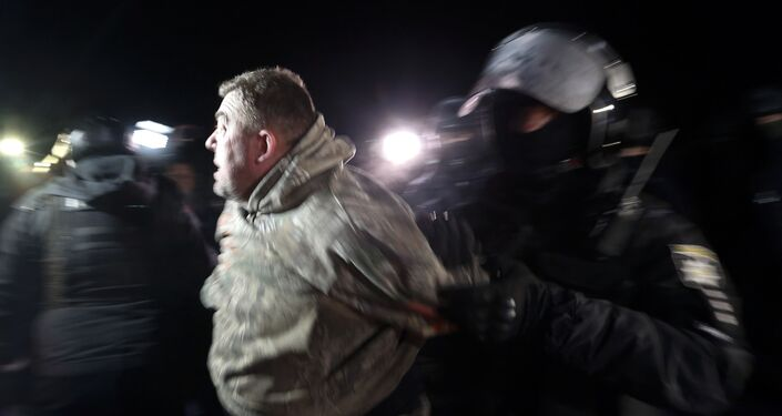 Polícia ucraniana prende manifestante durante protestos violentos na cidade de Novye Sarzhany, na Ucrânia, em 20 de fevereiro de 2020