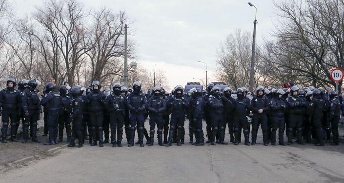 Policiais ucranianos formam barreira para impedir que manifestantes avancem sobre ônibus com passageiros evacuados da China, em Novye Sanzhany, na Ucrânia, em 20 de fevereiro de 2020