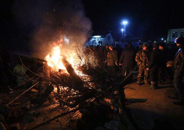 Manifestantes preparam barricada na entrada da cidade de Novye Sanzhany na Ucrânia, em 20 de fevereiro de 2020