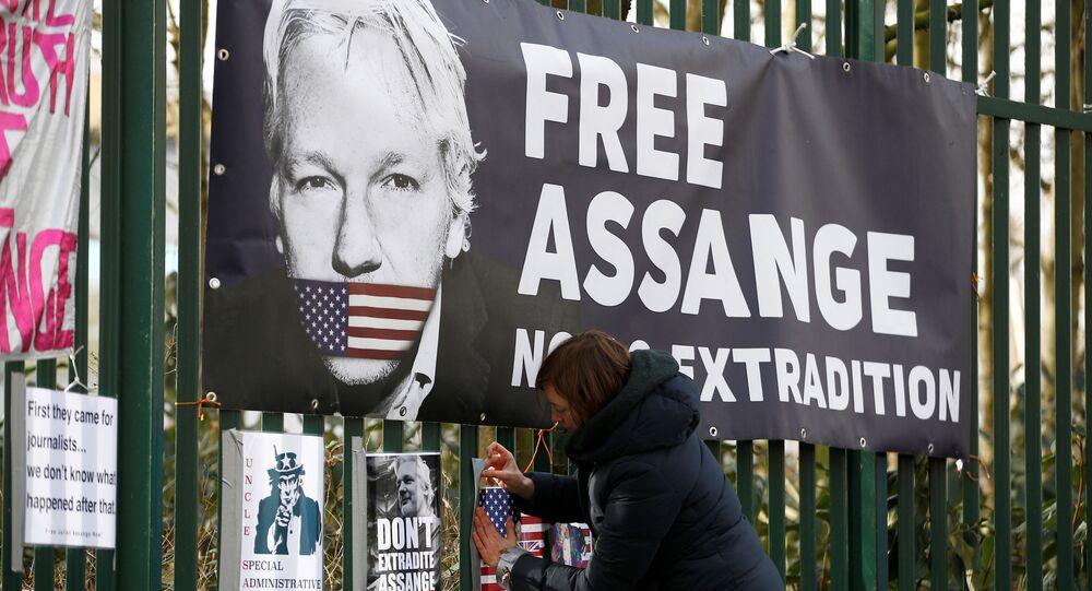 Apoiador do fundador do WikiLeaks, Julian Assange, afixa uma placa na cerca da Corte de Woolwich antes de uma audiência para decidir se Assange deve ser extraditado para os Estados Unidos, em Londres, Reino Unido, 25 de fevereiro de 2020