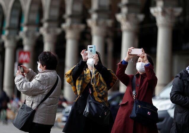 Pessoas com máscaras fazem foto em praça em Milão, na Itália