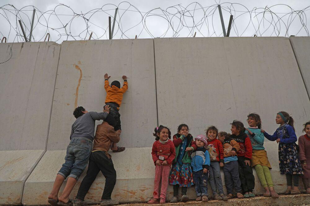 Crianças sírias tentam alcançar topo de muro na fronteira entre a Síria e a Turquia
