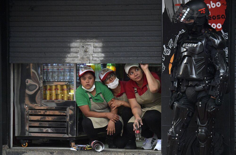 Mulheres observam protesto contra o presidente colombiano Iván Duque na capital, Bogotá, ao lado de um policial da Tropa de Choque