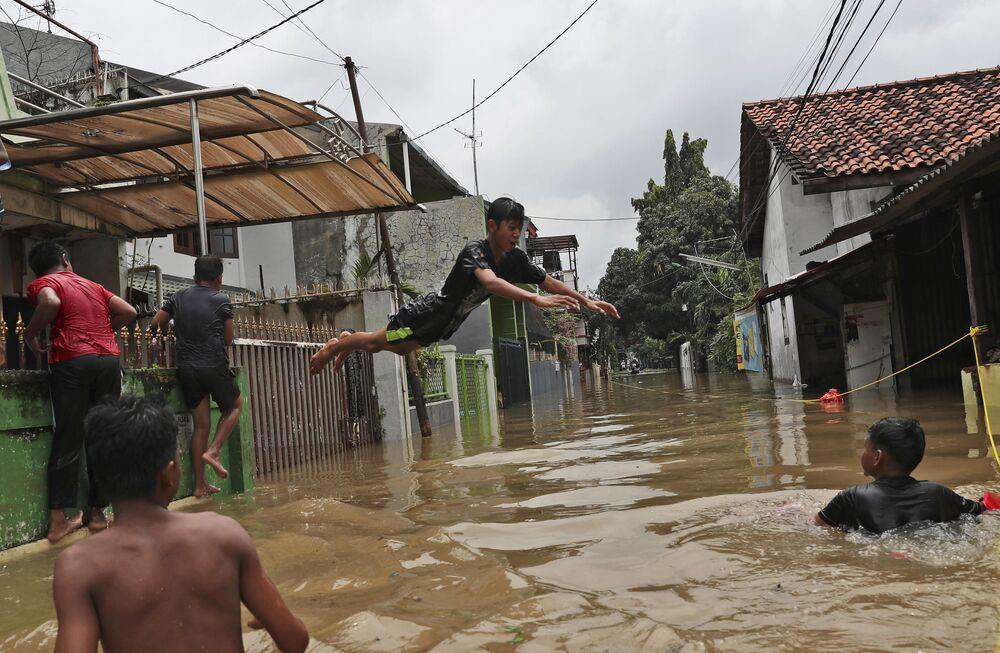 Crianças brincando em área alagada na capital indonésia, Jacarta, após chuvas noturnas