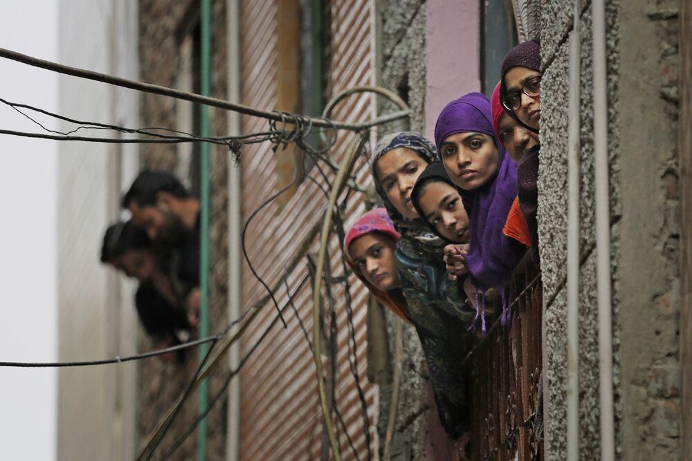 Muçulmanas indianas olham pela janela em uma rua de Nova Deli enquanto agentes de segurança do país passam pelo local