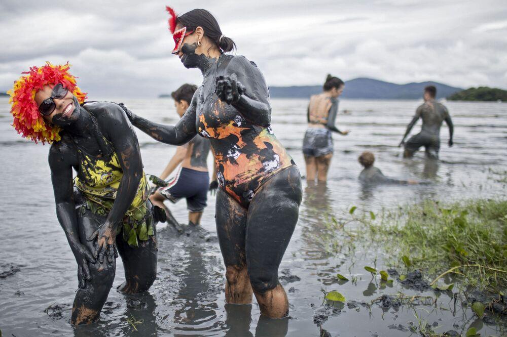 Mulheres passam lama em seus corpos durante a realização do Bloco da Lama no Carnaval de Paraty, no estado do Rio de Janeiro