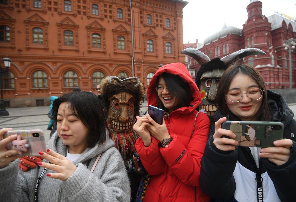 Turistas tiram fotos durante os festejos do tradicional Carnaval russo (Maslenitsa) na praça Manezhnaya em Moscou, Rússia