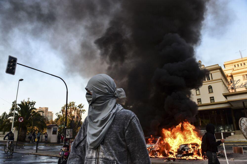 Manifestantes ao lado de carros em chamas durante protesto na frente do Hotel O'Higgins contra o presidente chileno, Sebastián Piñera, em Viña del Mar, Chile