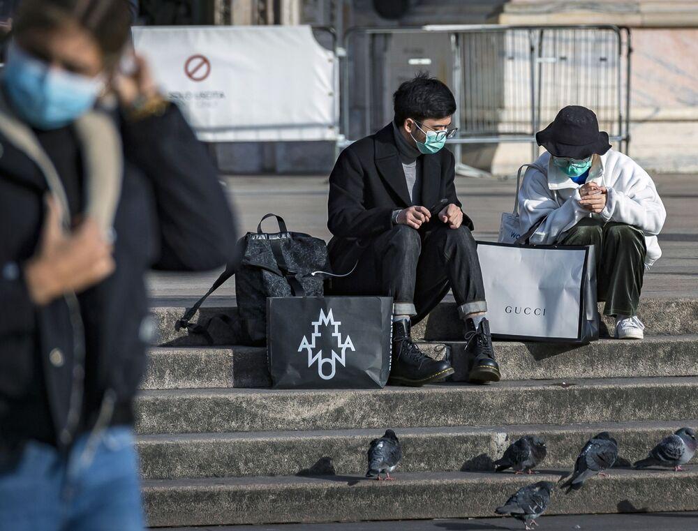 Turistas usando máscaras em uma das ruas da cidade italiana de Milão