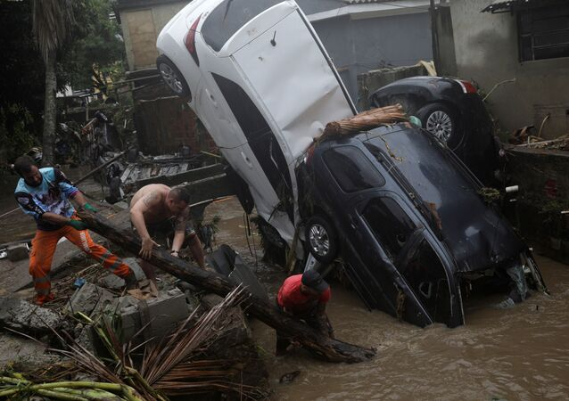 Moradores tentam remover carros danificados de um rio que transbordou no bairro de Realengo, no Rio de Janeiro, após fortes chuvas