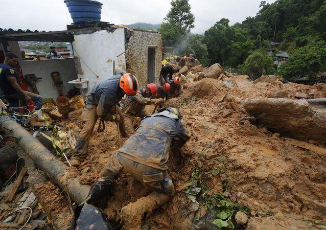 Equipes de resgate buscam vítimas de deslizamento de terra após fortes chuvas na cidade litorânea de Guarujá (SP)
