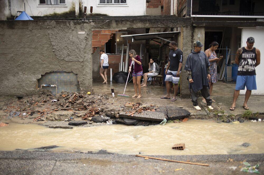Moradores observam estragos provocados pelas chuvas que causaram alagamento no bairro de Realengo, na Zona Oeste da capital fluminense
