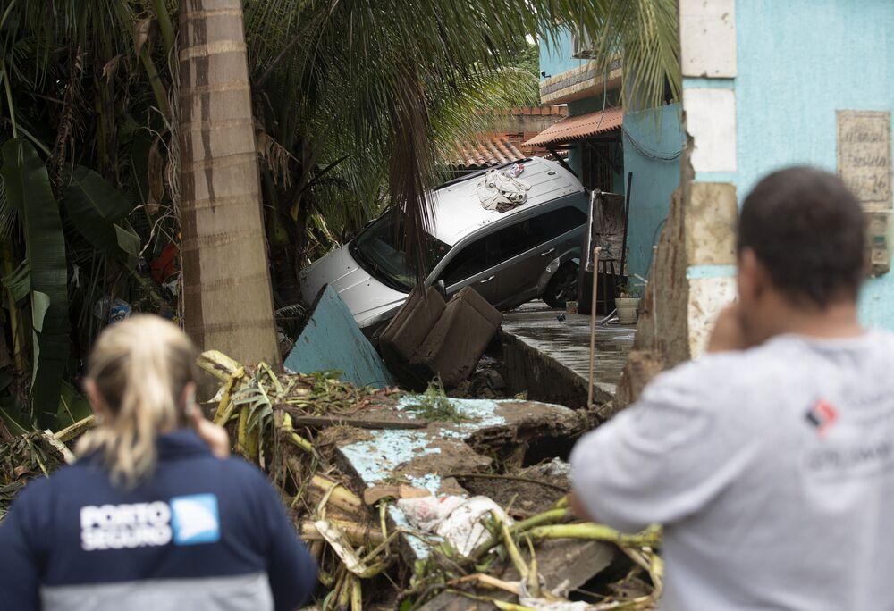 Carro quase de cabeça para baixo em quintal de casa no bairro de Realengo após fortes chuvas atingirem o local