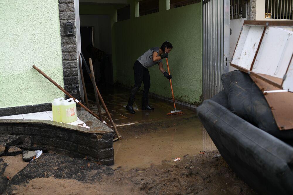 Mulher tira água suja de garagem de casa no bairro carioca de Realengo, na Zona Norte da cidade após fortes chuvas