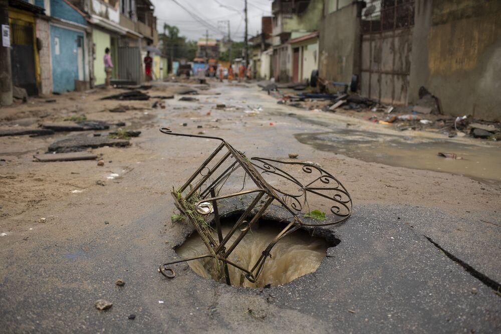 Cadeira de ferro cobre buraco aberto no asfalto em rua do bairro de Realengo