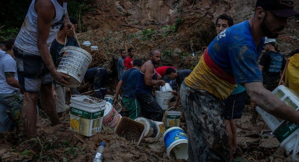 Moradores ajudam bombeiros nas buscas por sobreviventes no Morro da Barreira, em Guarujá (SP)