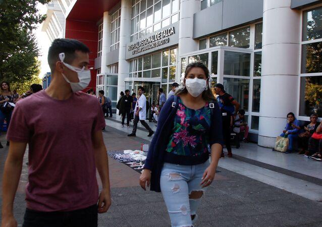 Cidadãos chilenos usam máscaras ao lado de fora do hospital regional de Talca, logo após a confirmação do primeiro caso chileno da doença na cidade.