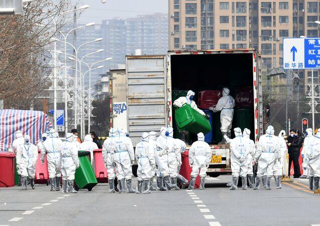 Trabalhadores em trajes de proteção participam da desinfecção do mercado de frutos do mar de Wuhan, onde se acredita ter surgido o novo coronavírus, na província de Hubei, China, 4 de março de 2020