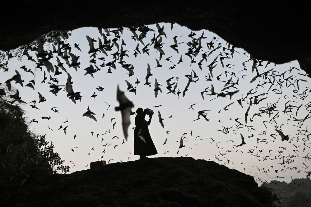 Mulher espanta morcegos de torre de controle em Mianmar, em 1º de março de 2020