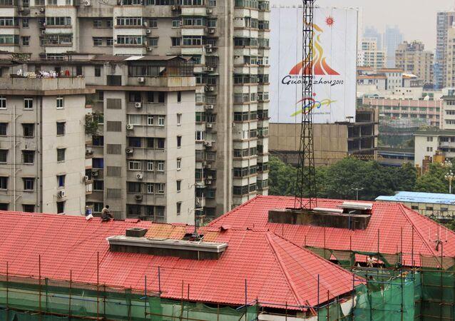Pedreiro trabalha no reparo de telhado de prédio na cidade de Guangzhou, na China (foto de arquivo)