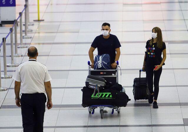 Usuários do aeroporto internacional de Buenos Aires usam máscaras para se proteger do coronavírus