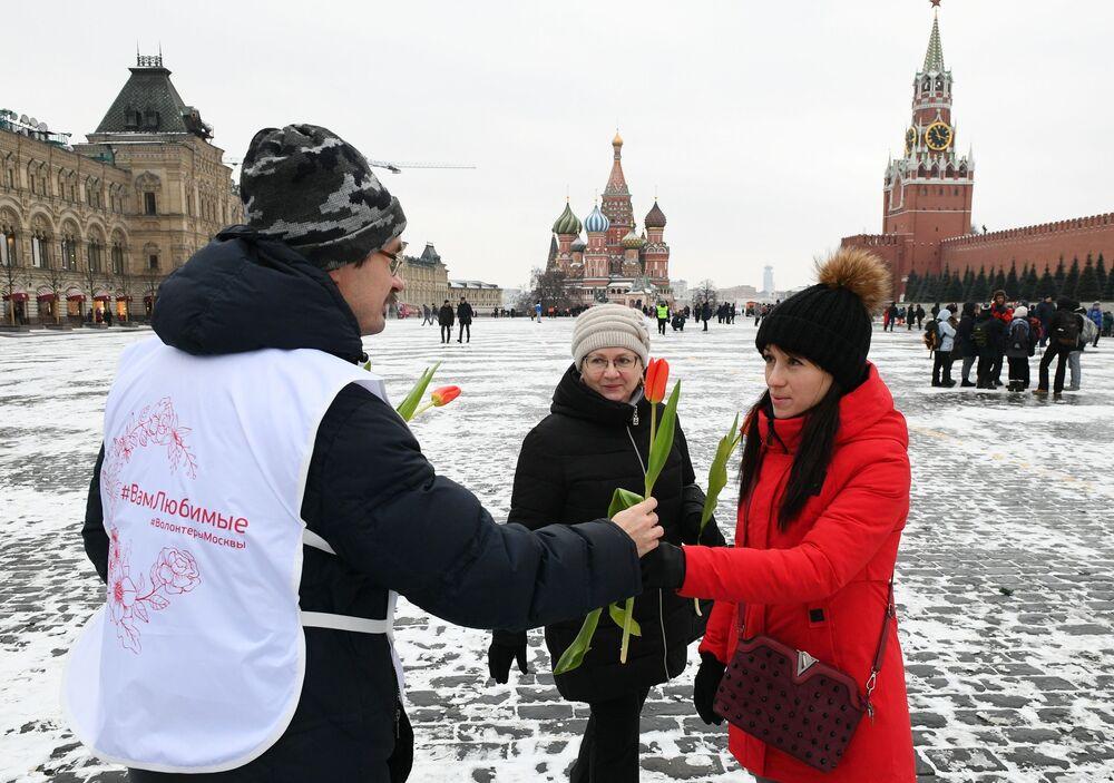 Voluntário oferece flores a mulheres na Praça Vermelha, em Moscou