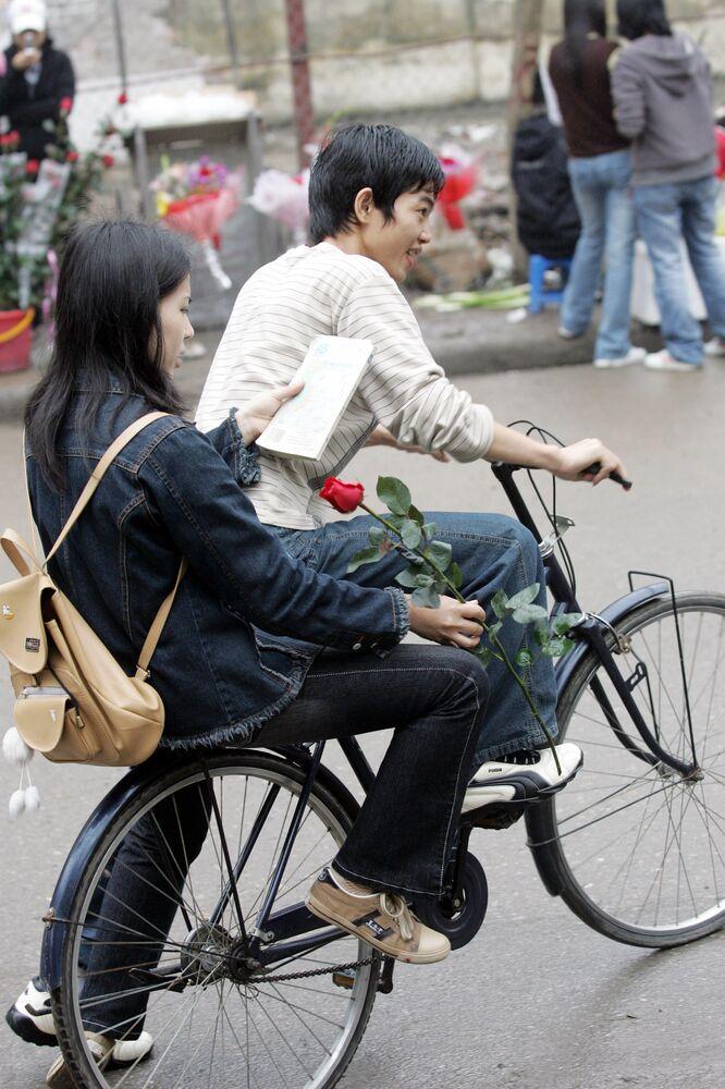 Menina com uma rosa em uma rua de Hanói em bicicleta, Vietnã, 8 de março de 2006. No Vietnã a festa se tornou o equivalente do Dia dos Namorados