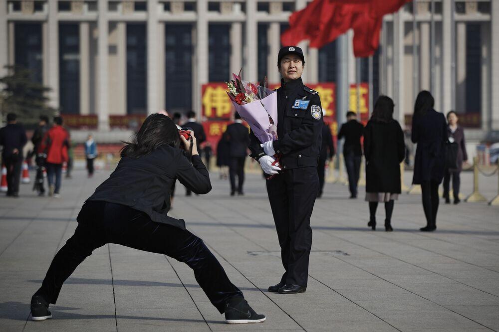 Mulher tirando foto de uma policial com flores na Praça da Paz Celestial, Pequim, China, em 8 de março de 2019