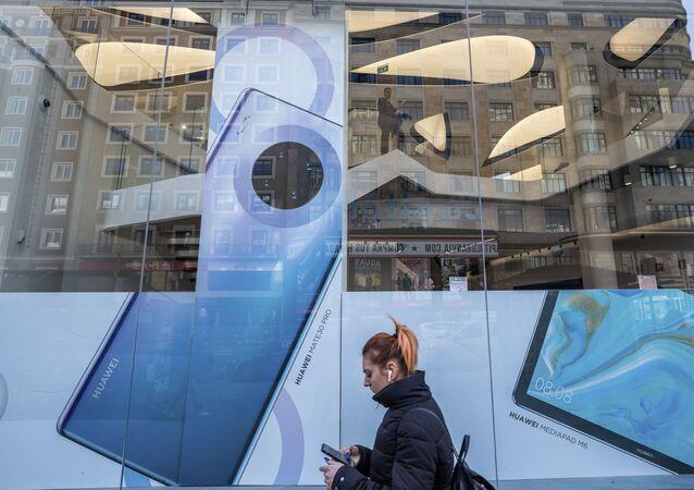 Mulher caminha diante de publicidade de um celular smartphone da Huawei