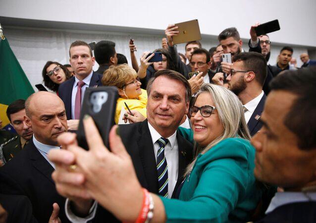Presidente do Brasil, Jair Bolsonaro, posa para selfie ao lado de apoiadora em Miami, EUA, 9 de março de 2020