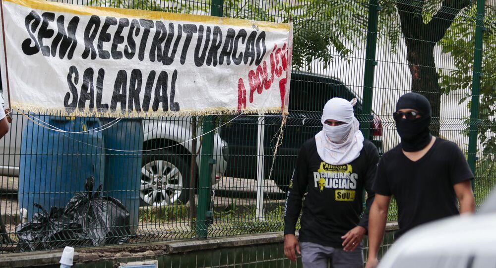 Policiais encapuzados passam por viaturas paradas durante a greve da PM no Ceará
