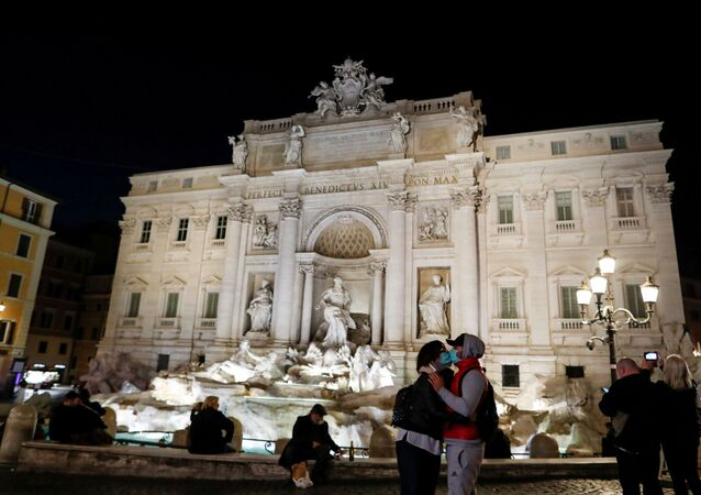 Casal se beija com máscaras em frente à Fontana di Trevi, em Roma, na Itália, 10 de março de 2020