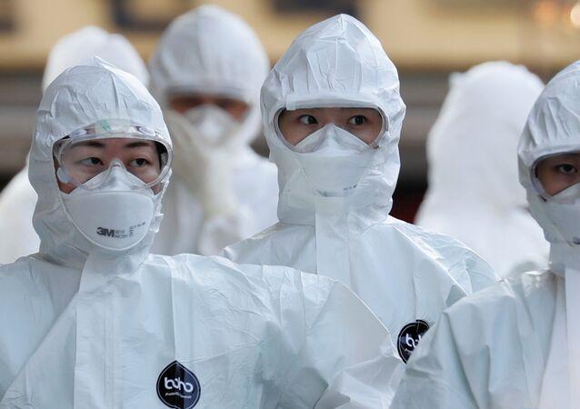 Médicos com equipamentos de proteção entram em hospital para tratar pacientes com coronavírus em meio ao aumento de casos confirmados de COVID-19 em Daegu, Coreia do Sul, 8 de março de 2020
