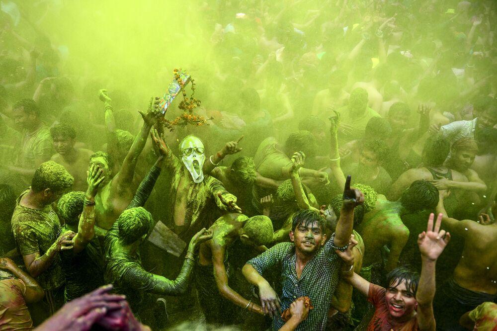 Foliões dançando durante a festividade da primavera Holi, na cidade indiana de Allahabad