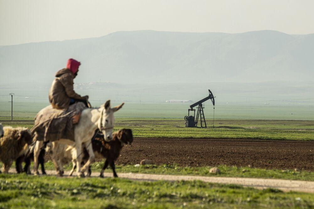 Pastor passa em frente a um poço de petróleo localizado na fronteira entre a Síria e a Turquia