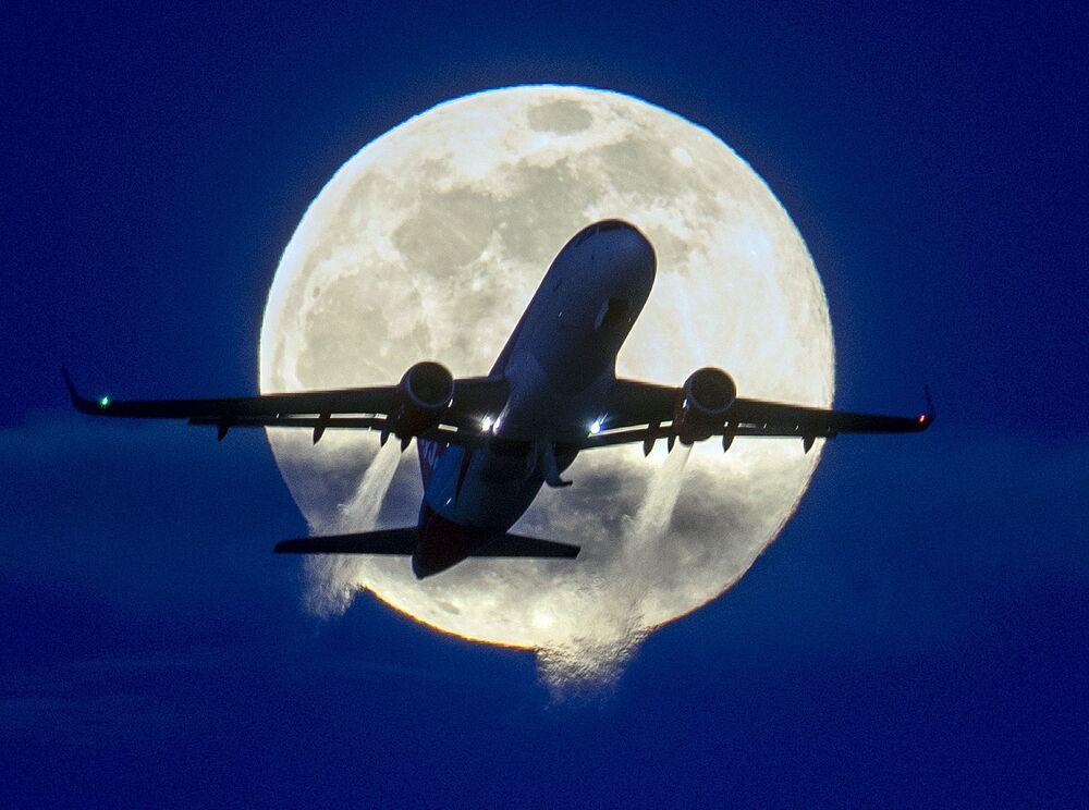 Avião sobrevoando o aeroporto alemão de Frankfurt, tendo ao fundo uma lua cheia