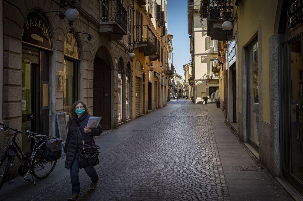 Mulher caminha com máscara em uma das ruas da comuna italiana de Novara