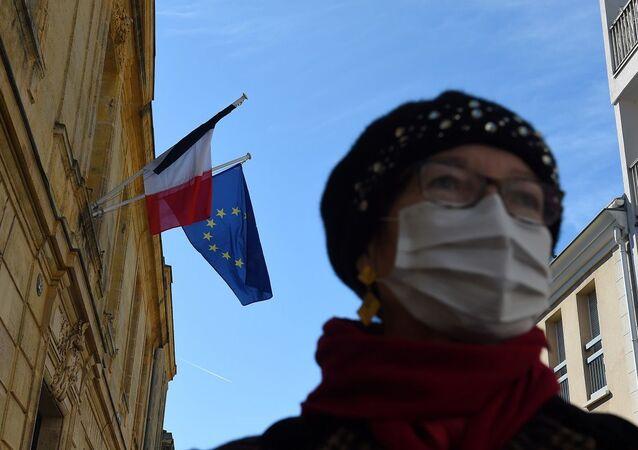 Mulher usando máscara enquanto pandemia de coronavírus atinge a Europa
