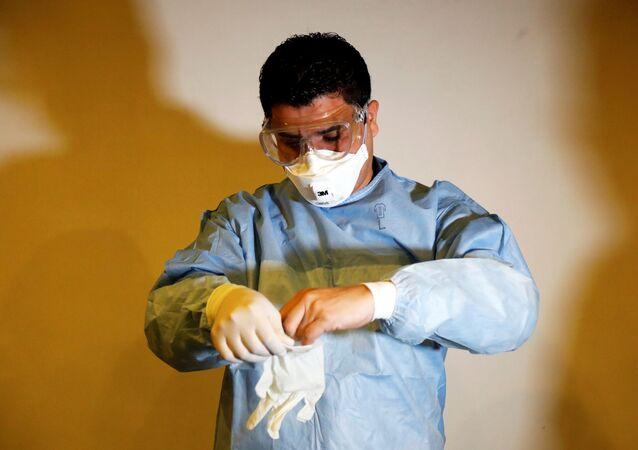 Um trabalhador de saúde na Guatemala explica como utilizar máscaras e luvas durante treinamento para checagem de suspeitos do novo coronavírus.