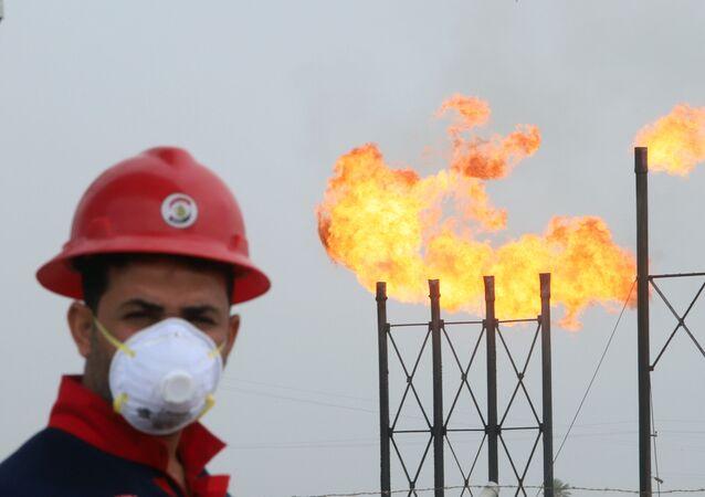 Funcionário usa máscara protetora em poço de petróleo no Iraque, em 15 de março de 2020