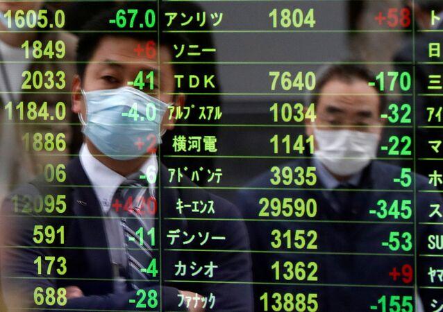 Pessoas usando máscaras de proteção facial, durante pandemia de coronavírus, observando tela exibindo os preços das ações em Tóquio, Japão, 17 de março de 2020
