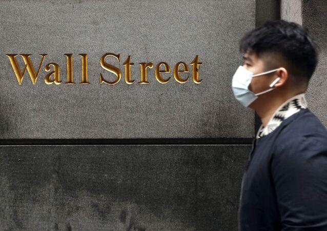 Homem usa máscara protetora enquanto caminha na Wall Street durante o surto de coronavírus em Nova York, EUA, 13 de março de 2020