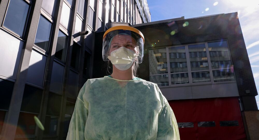 Médico com máscara e traje protetor em serviço no Hospital Onze Lieve Vrouw, Bélgica, 17 de março