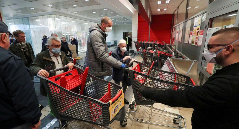 Guarda controla a entrada de um supermercado em Bruxelas, na Bélgica, que abre uma hora antes apenas para pessoas acima de 65 anos, em uma tentativa de proteger os mais vulneráveis contra os riscos de contágio do coronavírus, 18 de março de 2020