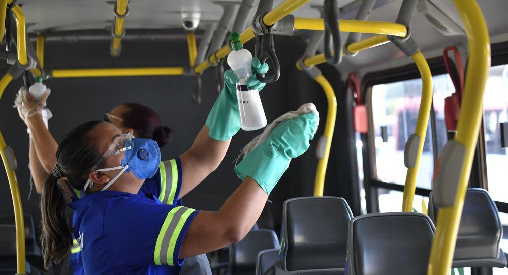 Mulher utiliza máscara de proteção facial como prevenção ao contágio do novo coronavírus (Covid-19) e realiza higienização em um ônibus na Rodoviária Central de Brasília (DF), nesta quarta-feira (18).