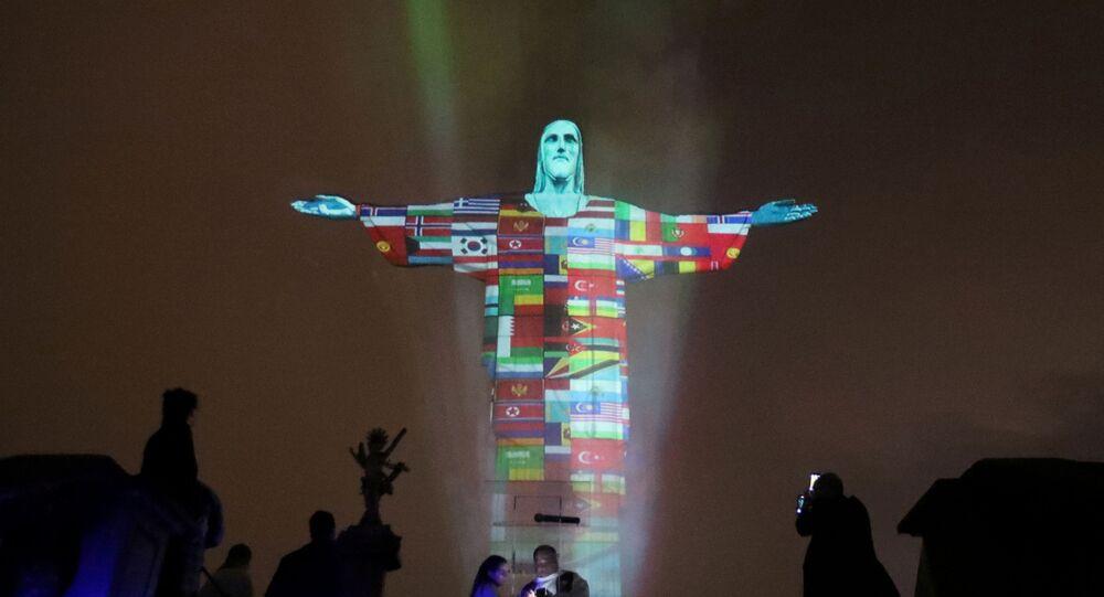 Estátua do Cristo Redentor é iluminada com a bandeira dos países afetados pelo novo coronavírus, Rio de Janeiro, 18 de março de 2020