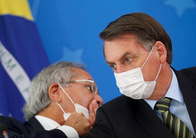O ministro da Economia do Brasil, Paulo Guedes (à esquerda) e o presidente brasileiro, Jair Bolsonaro (à direita), usam máscaras cirúrgicas durante coletiva de imprensa do governo sobre as medidas para combater a crise causada pelo novo coronavírus no país.